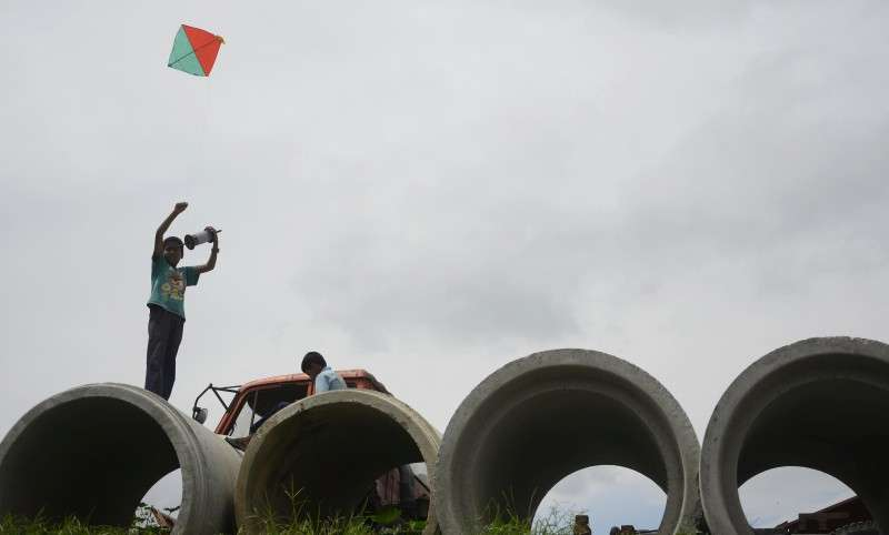 A child attempts to fly a kite by standing on top of a hume pipe in Teku. Photo: Ravi Maharjan/NBA